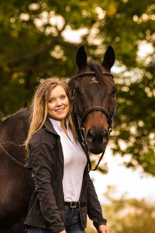 photo of woman standing beside horse